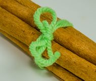 Cinnamon sticks tied with a piece of green yarn. Closeup of cinnamon sticks tied together with a piece of green yarn on white background Royalty Free Stock Photo