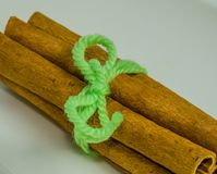 Cinnamon sticks tied with a piece of green yarn. Closeup of cinnamon sticks tied together with a piece of green yarn on white background Stock Photo
