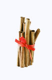 Cinnamon sticks tied with a red bow. On white background royalty free stock photography