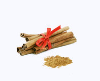 Cinnamon sticks tied with a red bow. On white background stock photos
