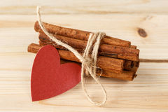 Cinnamon sticks tied with twine and red heart on a wooden background Royalty Free Stock Photography