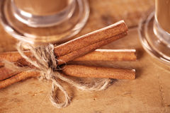 Cinnamon sticks tied up and coffee glasses Stock Photo