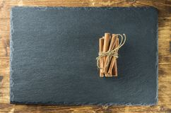 Cinnamon sticks top view on the background of slate and wood. Cinnamon sticks are connected with a coarse string of lezate on slate and wood surface Royalty Free Stock Photo