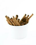 Cinnamon sticks in white cups. On white background royalty free stock image