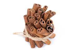 Cinnamon sticks on white surface bound with hemp rope. royalty free stock images