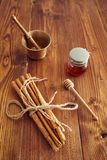 Cinnamon sticks. On a wooden table with bronze grinder Stock Image
