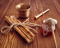 Cinnamon sticks. On a wooden table with bronze grinder Royalty Free Stock Images