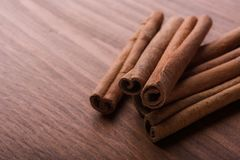 Cinnamon sticks on wooden background stock photography