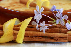 Cinnamon sticks wrapped in lemon peel with a bowl of rice pudding. And decorated with flowers Stock Photo