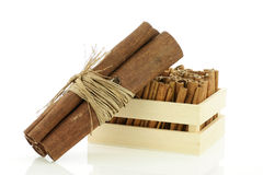 Cinnamon sticks wrapped together and a wooden crate. Royalty Free Stock Photography