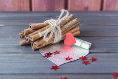 Cinnamon stocks with silver heart decorated with cloth pin and red sparkling stars on wooden planks St.Valentine's Day. Toned selective focus Royalty Free Stock Photography