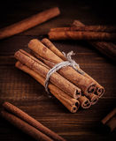 Cinnamon on the wooden background. Royalty Free Stock Images