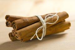 Cinnamon on the wooden surface Stock Photos