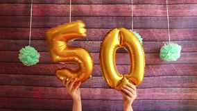 Cinqüênta aniversário feliz com os balões de ar dourados do número 50, celebração do aniversário filme
