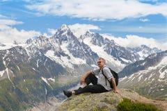 Cinqüênta anos de turistas que sentam-se em uma rocha contra cimeiras da montanha Imagem de Stock