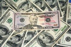 Cinqüênta dólares entre cem contas de dólar Foto de Stock