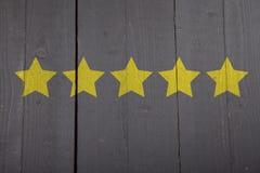 Cinq étoiles jaunes de rang sur le fond en bois photo stock
