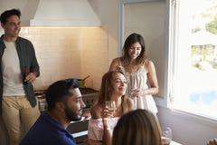 Cinq amis accrochant ensemble le boire dans la cuisine Image libre de droits