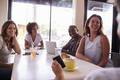Cinq amis adultes s'asseyant dans un café, au-dessus de vue d'épaule images stock