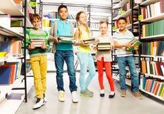 Cinq amis avec des piles des livres dans la bibliothèque Photos stock