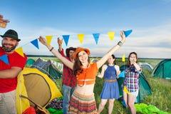 Cinq amis dansant en dehors des tentes au terrain de camping Photo stock