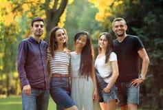 Cinq amis des jeunes regardant l'appareil-photo en parc ensoleillé Photographie stock libre de droits
