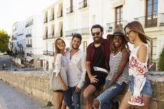 Cinq amis des vacances en Ibiza à l'allure de citadin à l'appareil-photo Images stock