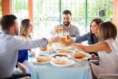 Cinq amis faisant le pain grillé à un barbecue Images libres de droits