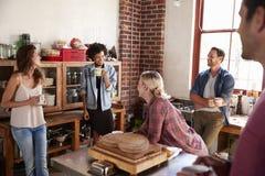 Cinq amis heureux parlant dans la cuisine, foyer sélectif Photo stock