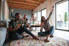 Cinq amis heureux s'asseyant dans la maison et mangeant de la pizza Photographie stock