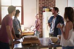 Cinq amis parlent la position dans la cuisine, se ferment  Photographie stock libre de droits