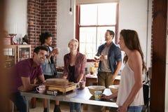 Cinq amis riant au-dessus du café dans la cuisine, se ferment  Photographie stock