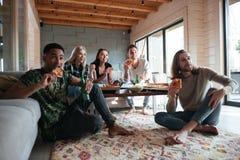 Cinq amis s'asseyant dans la maison et mangeant de la pizza Photos libres de droits