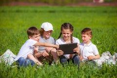 Cinq amis s'asseyant sur l'herbe Photographie stock