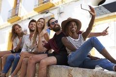 Cinq amis s'asseyant sur un mur dans Ibiza prenant un selfie Images stock
