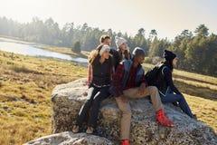 Cinq amis s'asseyant sur une roche dans la campagne regardent loin Images stock
