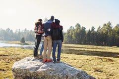Cinq amis se tenant sur une roche dans la campagne, vue arrière Images stock
