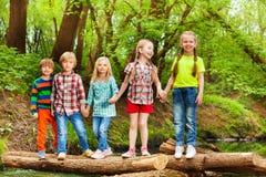 Cinq amis se tenant tenants des mains sur le pont de rondin Images stock