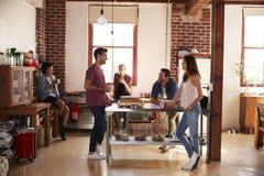 Cinq amis traînant au-dessus du café dans la cuisine, intégrale Photographie stock