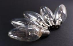 Cinq ampoules cassées sur le fond noir Images stock