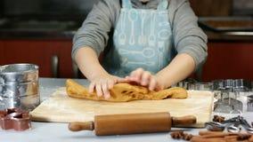 Cinq années de garçon malaxe la pâte pour des biscuits de pain d'épice de Noël Metal les coupeurs, la farine et le stylo de roule banque de vidéos