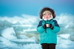 Cinq années mignonnes de garçon buvant du thé chaud à la mer congelée par hiver Image libre de droits