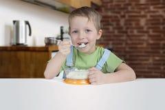 Cinq ans de garçon mange du gruau sur la cuisine Image libre de droits