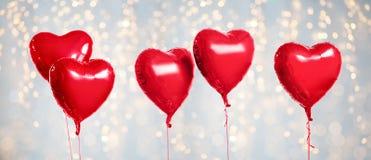 Cinq ballons en forme de coeur rouges d'hélium sur le blanc image libre de droits