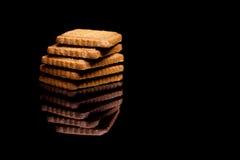 Cinq biscuits sur le fond réfléchi noir Photos stock