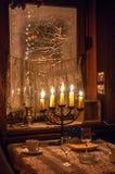 Cinq bougies brûlant dans le menorah sur une table sur le premier plan et la fenêtre givrée avec l'arbre neigé dehors Images stock