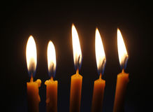 Cinq bougies brûlantes de cire sur la fin noire de fond  Images stock