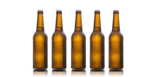 Cinq bouteilles à bière en verre d'isolement sur le fond blanc Image libre de droits