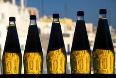 Cinq bouteilles contre éclairées avec le liquide ambre Images stock