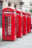 Cinq cabines téléphoniques rouges de Londres toutes dans une rangée Photographie stock libre de droits